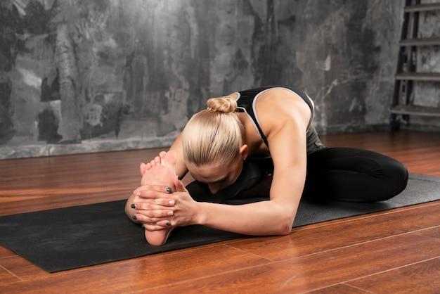Volle schussfrau, die zu hause yoga tut