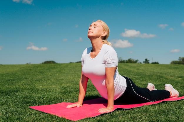 Volle schussfrau in der yogahaltung draußen