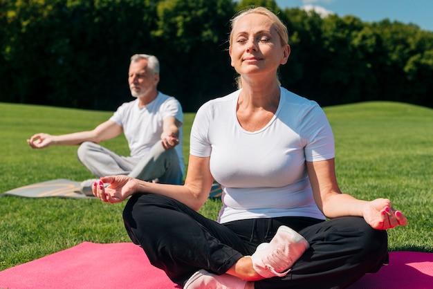 Volle schussleute, die auf yogamatten meditieren