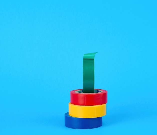 Volle spulen des mehrfarbigen isolierbands auf einem blauen hintergrund