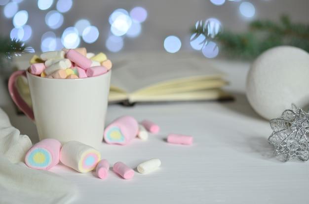 Volle tasse bunte marshmallows und weihnachtskugel auf bokeh hintergrund