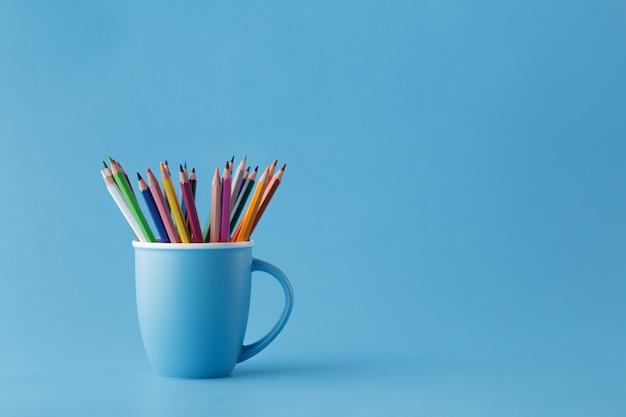 Voller becher mit scharfen farbstiften auf monochromatischem blau