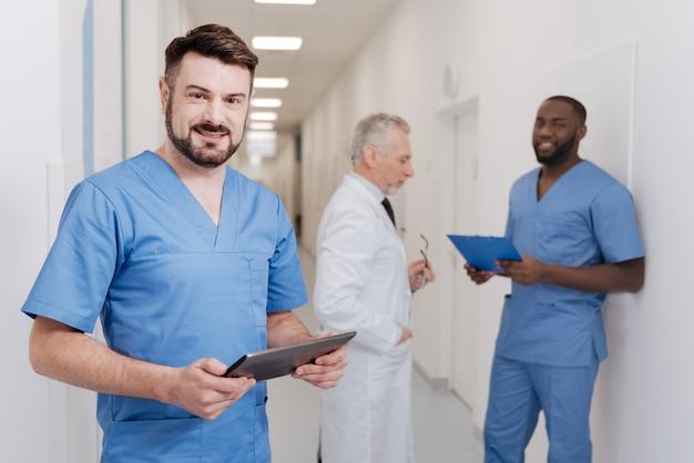 Voller begeisterung bei der arbeit. charmanter junger bärtiger arzt, der im krankenhaus steht und tablette hält, während andere kollegen arbeitsaspekte im hintergrund besprechen