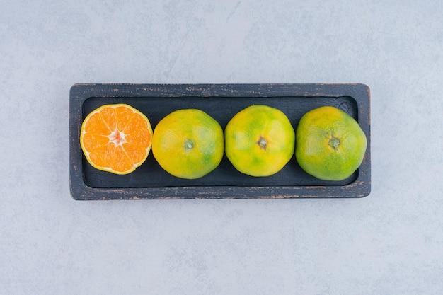 Voller dunkler teller mit sauren mandarinen auf weiß