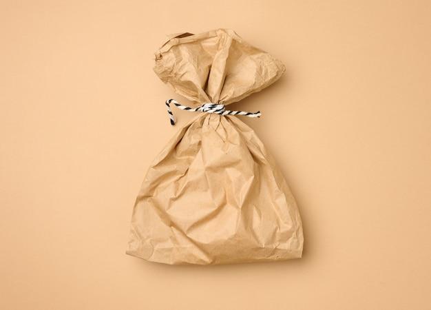 Voller einweg-lebensmittelbeutel aus braunem papier auf beigem hintergrund, konzept der lieferung und bestellung, draufsicht, kein abfall