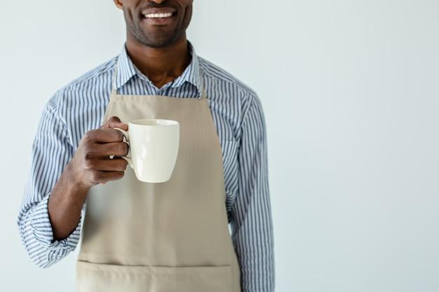 Voller energie. fröhlicher afroamerikanischer kellner, der eine tasse kaffee hält, während er seine arbeit genießt