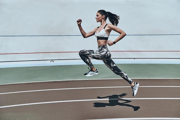 Voller energie. volle länge der jungen frau in sportkleidung, die beim training im freien läuft