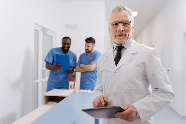 Voller freude. älterer fröhlicher professioneller arzt, der in der klinik arbeitet und in der nähe des krankenschwesterbüros steht, während er gerät hält