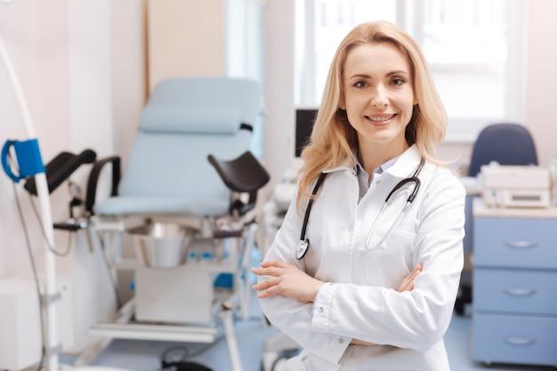 Voller freudiger gefühle bei der arbeit. positiv begeisterte qualifizierte gynäkologin, die im gynäkologie-kabinett steht, positivität ausdrückt und arbeitsverantwortung genießt