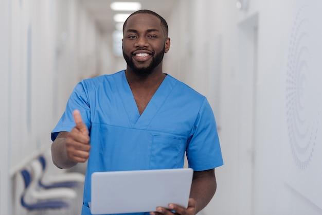 Voller fröhlicher gefühle. charismatisch lächelnder afroamerikanischer praktizierender, der in der klinik steht, während daumen hoch zeigt und laptop hält