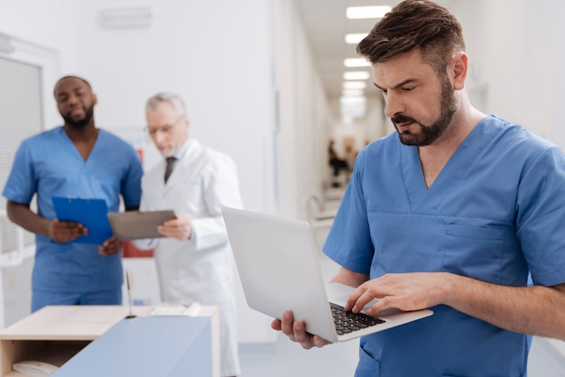 Voller interesse. reifer konzentrierter professioneller arzt, der in der klinik arbeitet und in der nähe des krankenschwesterbüros steht, während er einen laptop benutzt