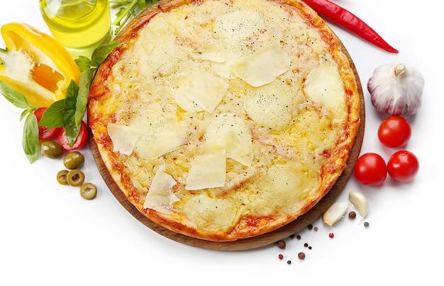 Voller käsepizza auf holzbrett mit gemüse, nahaufnahme