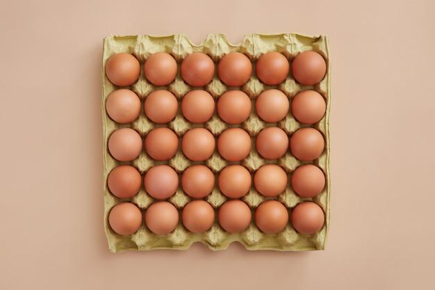 Voller karton der frischen eier lokalisiert auf beigem hintergrund