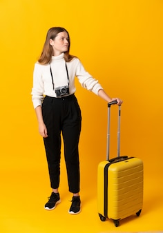 Voller körper des reisendjugendlichmädchens mit koffer über dem lokalisierten gelben schauen zur seite