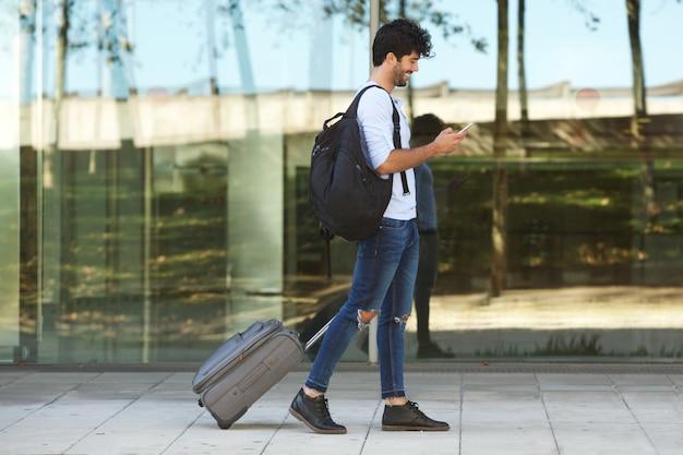 Voller körper gutaussehender mann, der draußen mit koffer und intelligentem telefon geht