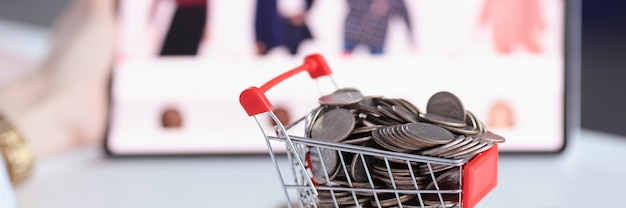 Voller korb mit münzen auf dem hintergrund eines online-shops mit vor- und nachteilen des online-shoppings von waren
