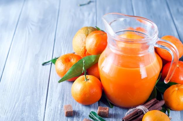 Voller krug mandarinesaft mit mandarinen