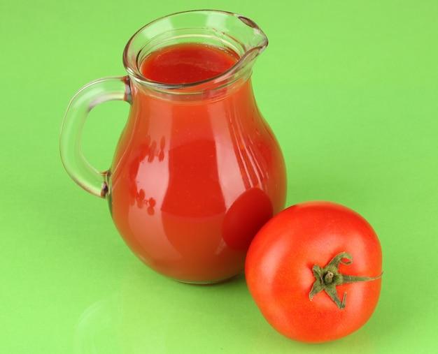 Voller krug tomatensaft, auf farbigem hintergrund
