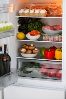 Voller kühlschrank für gesunde lebensmittel, richtige ernährung der keto-diät-kühlschrank mit gesunden lebensmitteln im kühlschrank fleisch mit gemüse das konzept der richtigen ernährung roter fisch