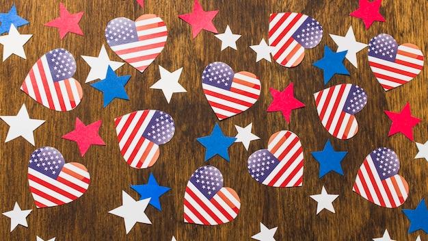 Voller rahmen von amerikanischen flaggen und von sternen der herzform auf hölzernem schreibtisch