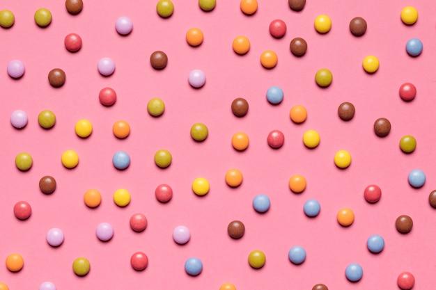 Voller rahmen von bunten mehrfarbigen edelstelsüßigkeiten auf rosa hintergrund