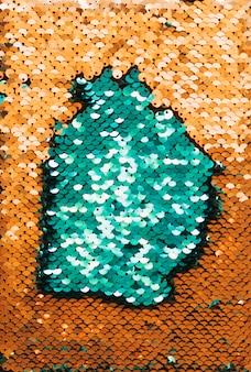Voller rahmenzusammenfassungshintergrund von grünen und goldenen reflektierenden pailletten