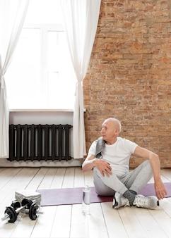 Voller schuss älterer mann auf yogamatte