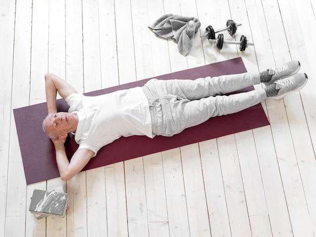 Voller schuss älterer mann, der auf yogamatte liegt