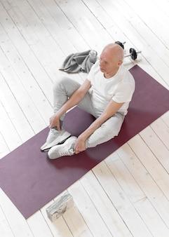 Voller schuss älterer mann, der auf yogamatte sitzt