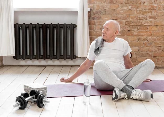 Voller schuss älterer mann mit yogamatte