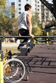 Voller schuss behinderter mann, der arme im park trainiert