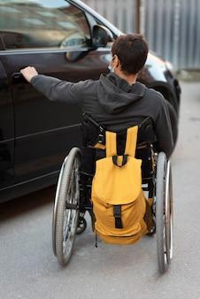 Voller schuss behinderter mann, der autotür öffnet