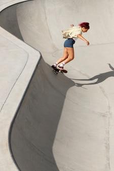 Voller schuss coole frau, die spaß auf dem skateboard hat