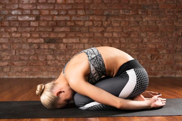 Voller schuss, der frau auf yogamatte sich duckt