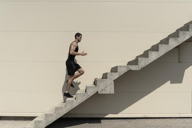Voller schuss des gesunden athletischen mannes, der auf treppen klettert.