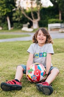 Voller schuss des jungen im gras mit fußball