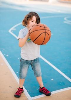 Voller schuss des kindes basketball spielend