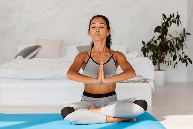 Voller schuss entspannte frau, die yoga praktiziert