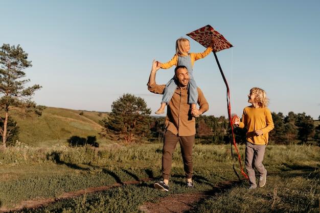 Voller schuss glückliche familie, die mit drachen spielt