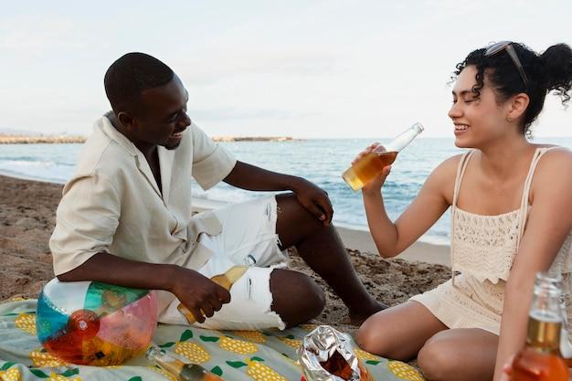 Voller schuss glückliche freunde, die am strand sitzen
