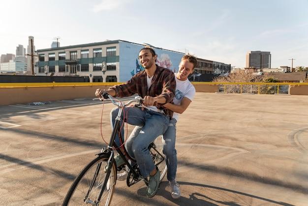 Voller schuss glückliche männer, die fahrrad fahren