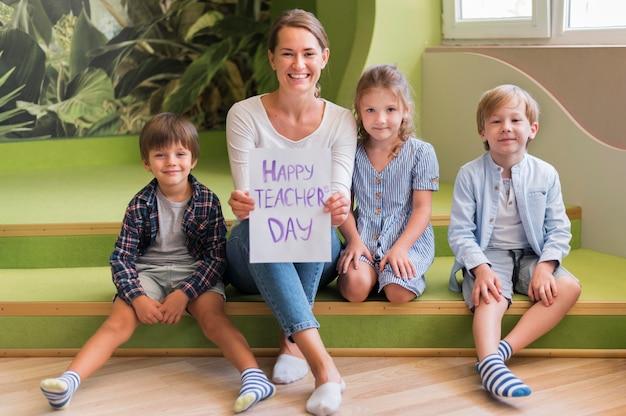 Voller schuss glücklicher lehrer, der mit kindern aufwirft