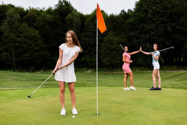Voller schuss hübsche mädchen, die golf spielen