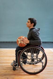 Voller schuss junger behinderter mann, der basketball hält