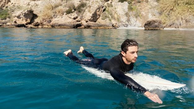 Voller schuss junger mann auf surfbrett