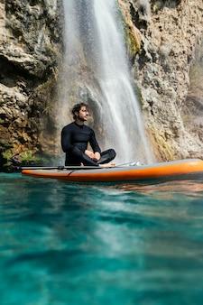 Voller schuss junger mann, der auf surfbrett sitzt