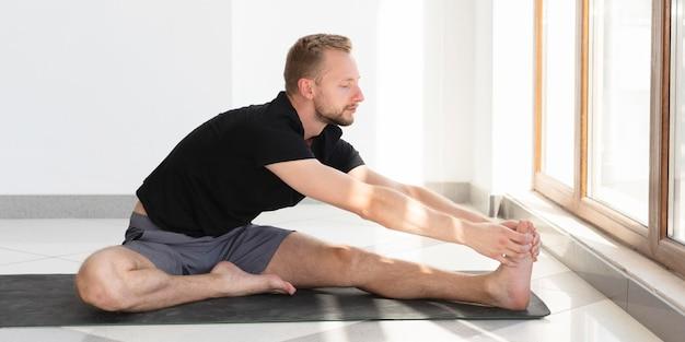 Voller schuss junger mann, der auf yogamatte streckt