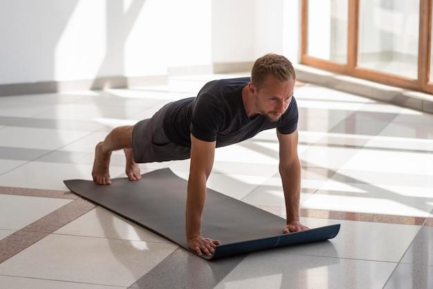 Voller schuss junger mann, der yoga drinnen praktiziert