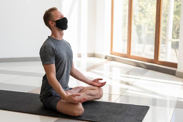 Voller schuss junger mann mit gesichtsmaske, die yoga drinnen praktiziert