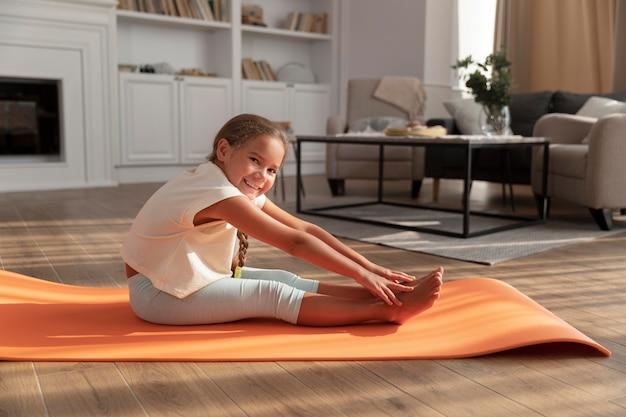 Voller schuss kind, das sich auf yogamatte ausdehnt